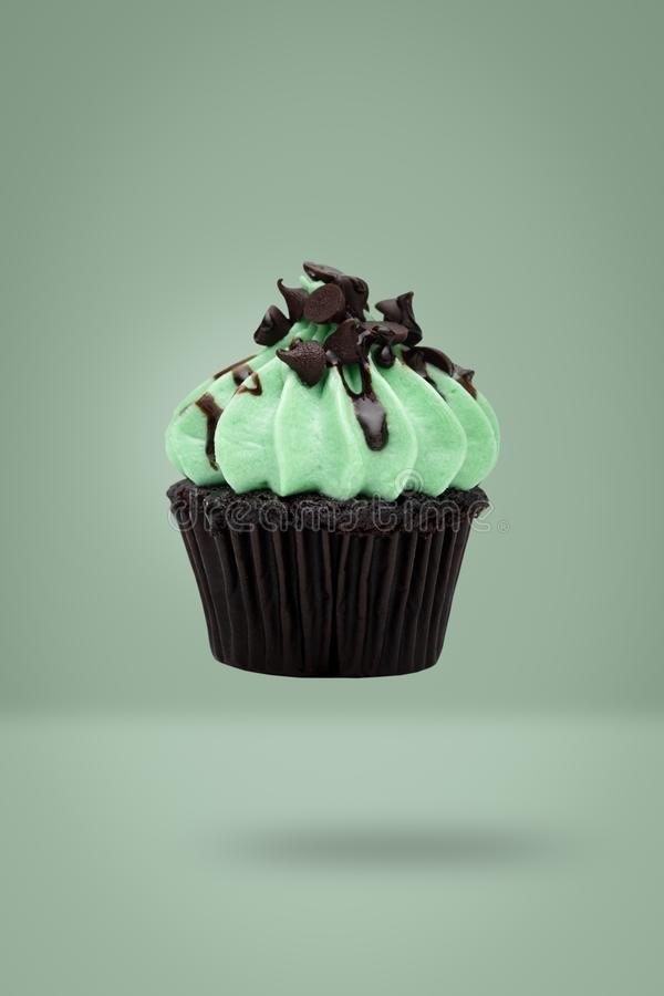 Mint cupcake flying on green background, idea minimal concept for new year and christmas holliday.  royalty free stock photography