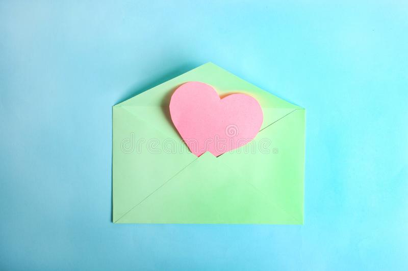 Mint envelope with pink heart. On blue background. Top view, copy space. Concept Valentine`s Day, declaration of love stock images