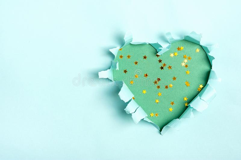 Mint green Heart shape hole through blue paper Flat lay Happy Valentines day concept royalty free stock photography