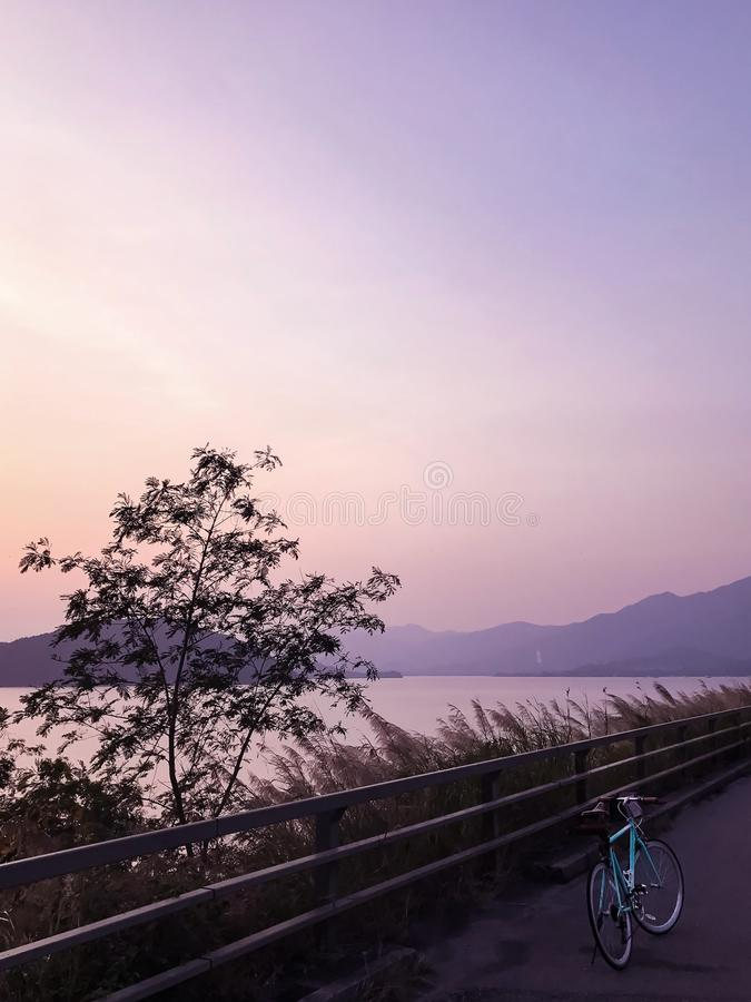 Mint green retro bicycle, road frame, mountain, lake and gradient sky. At sunset royalty free stock photos