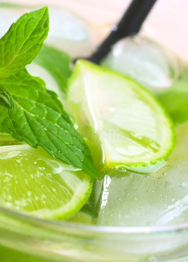 Mint, Lime, Ice Cube. Refreshing drink with mint leaves, lime wedges and ice cubes with black drinking straw in the back (Selective Focus, Focus one third into stock photo