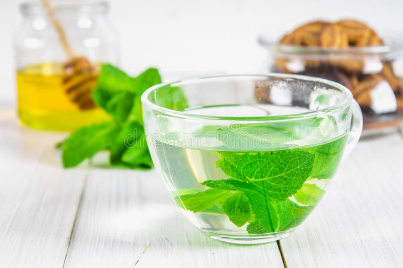 Mint tea in a cup, honey jar, cookies on a white wooden table. stock images