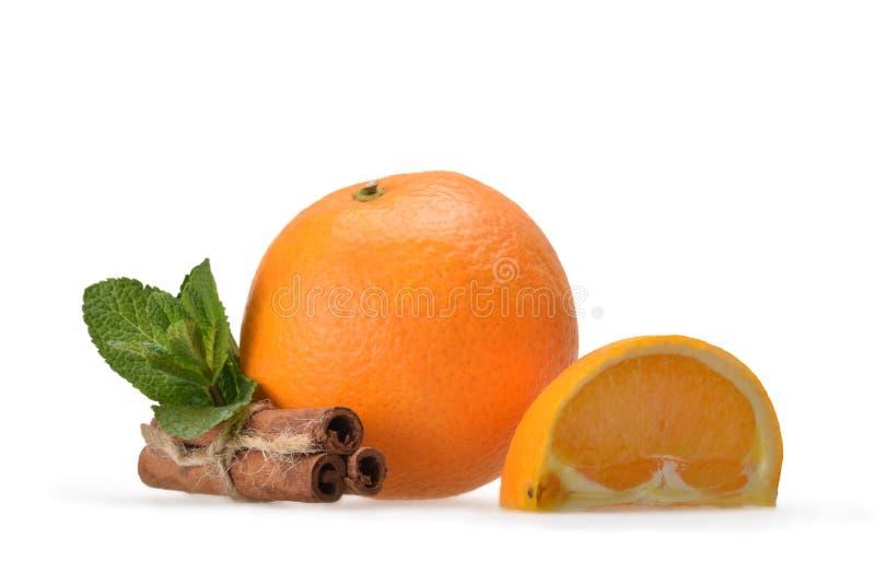 Mint, three cinnamon sticks, ripe orange orange and quarter orang royalty free stock images