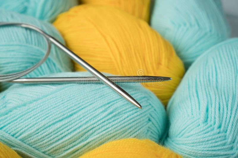 Mint and yellow acrylic yarn with knitting needles. Beautiful mint and yellow yarn for knitting baby clothes. For yarn, children` royalty free stock photo