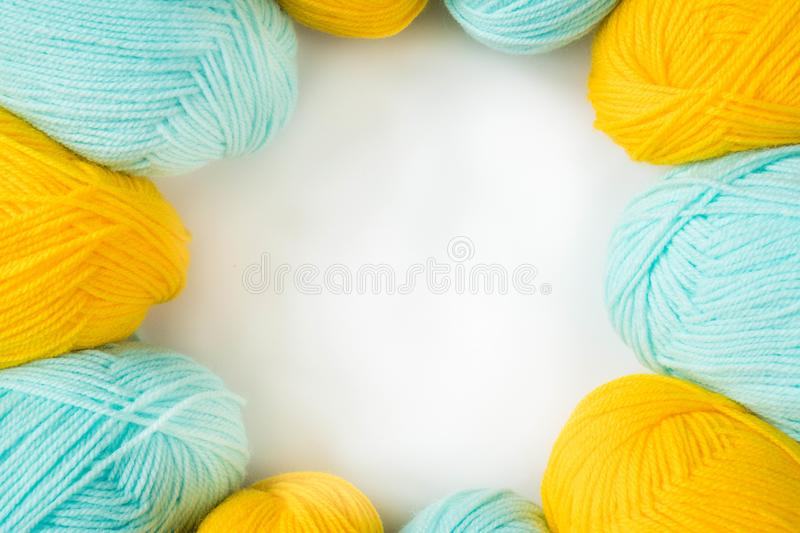 Mint and yellow acrylic yarn on a white background, lined up in a circle, with copyspace. Beautiful yarn for knitting baby clothes stock photo
