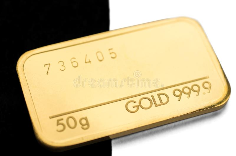 Minted gold bar weighing 50 grams on a black and white background. stock photography