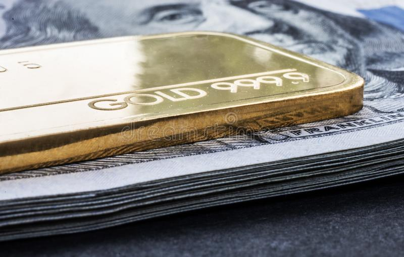 Minted gold bar weighing 50 grams 999.9, fineness against the background of a dollar bills royalty free stock photography
