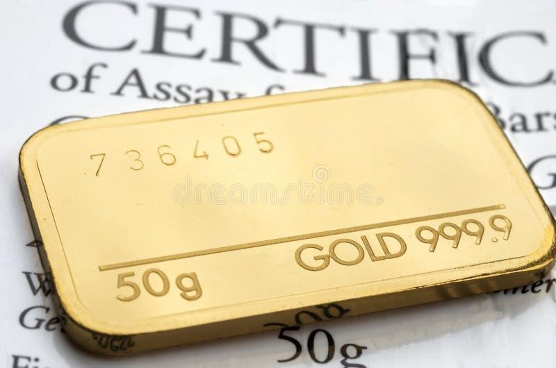 Minted guld- stång som väger 50 gram finhet 999 9 på bakgrunden av ett certifikat fotografering för bildbyråer
