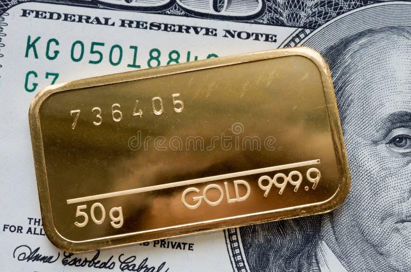 Minted guld- stång som väger 50 gram mot bakgrunden av dollarräkningen fotografering för bildbyråer