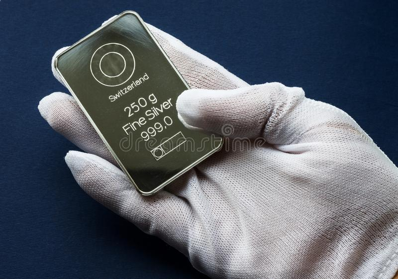 Minted silver bar in the hand, dressed in a white protective glove. On a blue background royalty free stock photography