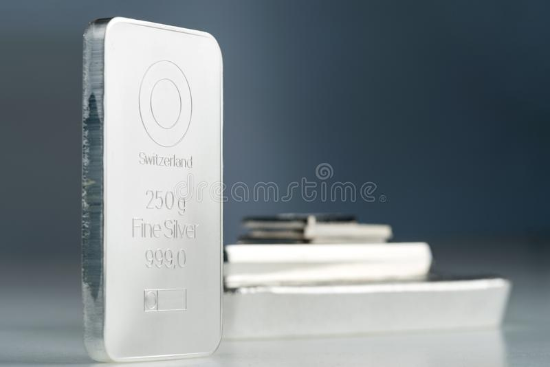 Minted silver bullion weighing 250 gr. Minted silver bar weighing 250 grams against a background of a stack of various silver bars. Selective focus royalty free stock images