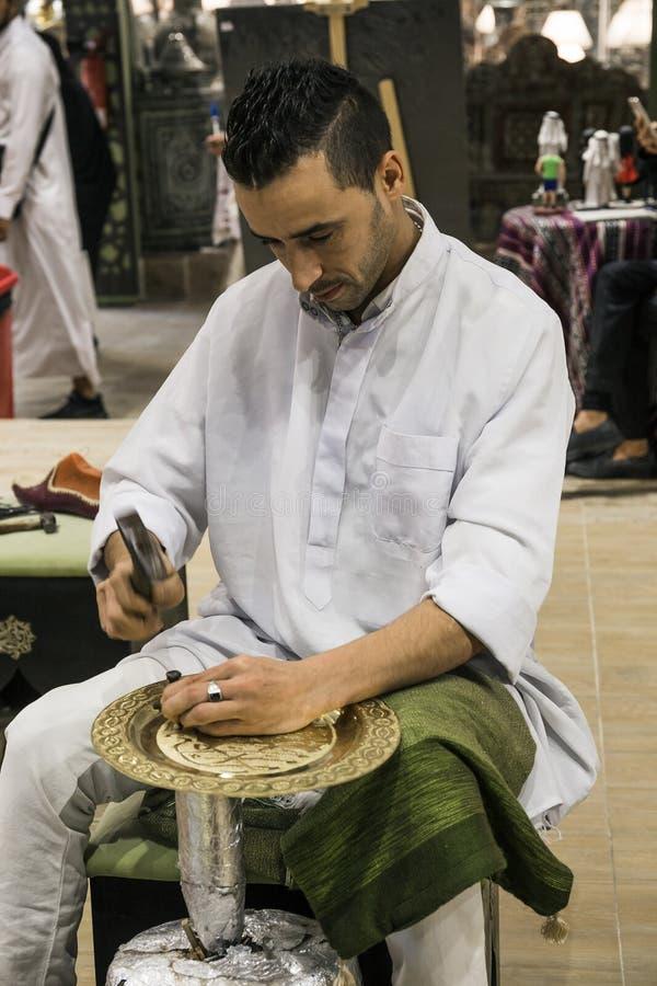Minter artisanaal in nationale kleren in het paviljoen van Turkije binnen stock afbeelding