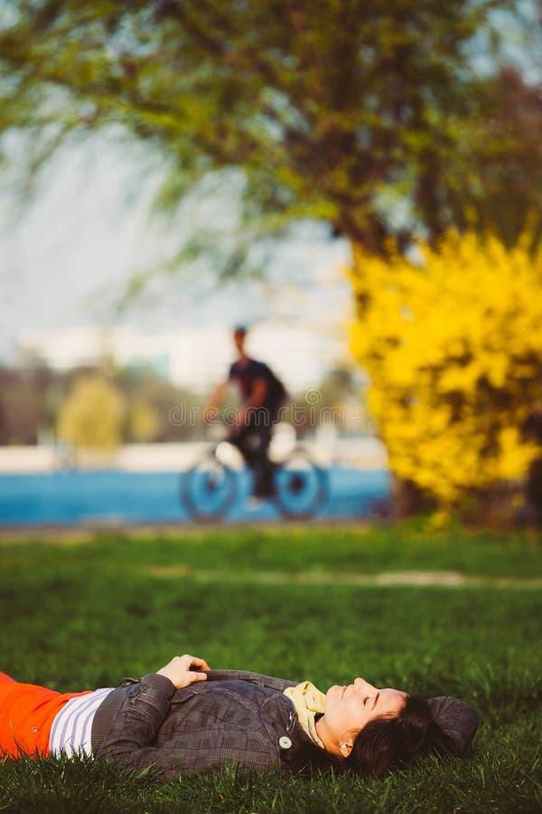 Mintiendo en la hierba, en el parque foto de archivo libre de regalías