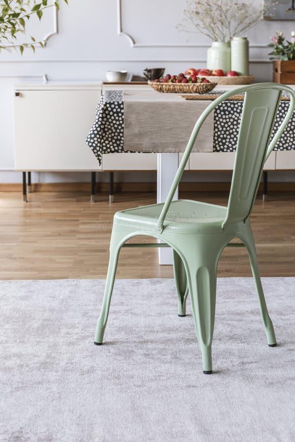 Mintkaramellgräsplanstol på grå matta på tabellen i lantlig matsal som är inre med lampan och väggen med stöpningen Verkligt foto royaltyfria bilder