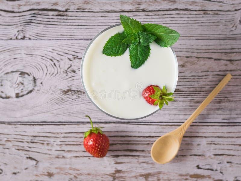 Mintkaramellsidor och jordgubbebär i en bunke av yoghurt arkivfoton