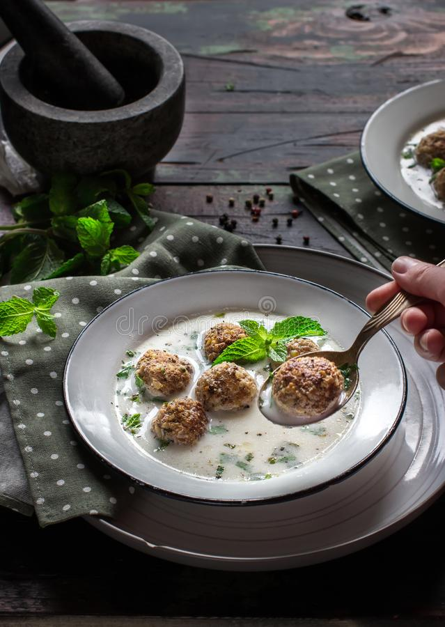 Minty turkish yogurt soup with meatballs. Minty turkish yogurt soup with meatballs on wooden table. Selective focus royalty free stock photo