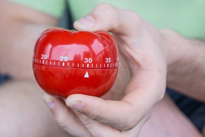 Minuterie rouge mécanique de cuisine de tomate réglée à 30 minutes, saisies par une main images stock