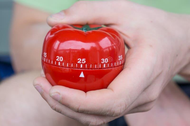 Minuterie rouge mécanique de cuisine de tomate réglée à 25 minutes, saisies par une main photos stock