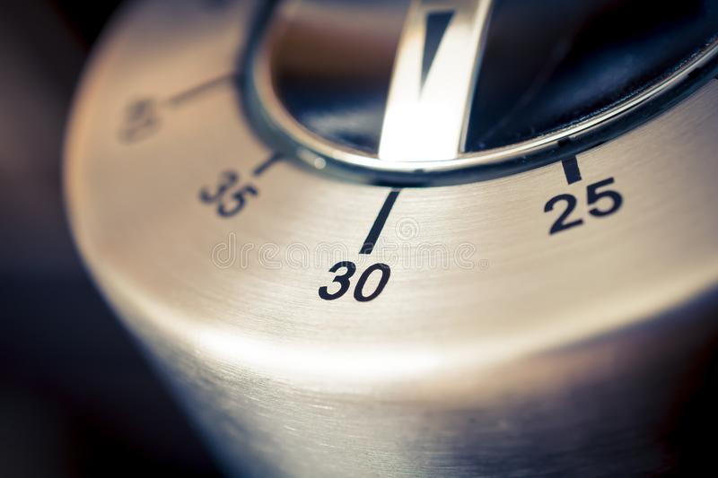 30 Minutes - Macro Of An Analog Chrome Kitchen Timer With Dark Background stock images