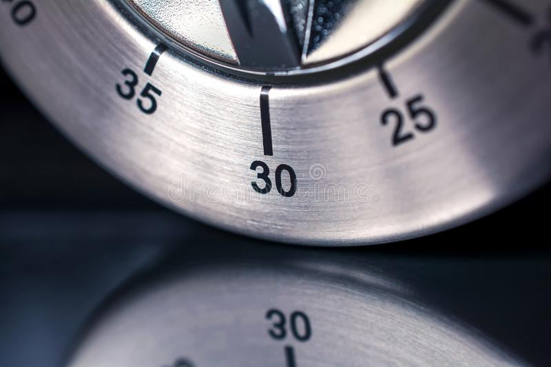 30 Minutes - Macro Of An Analog Chrome Kitchen Timer With Dark Background And Reflection royalty free stock image