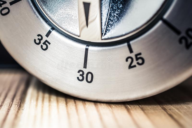 30 Minutes - Macro Of An Analog Chrome Kitchen Timer On Wooden Table royalty free stock images