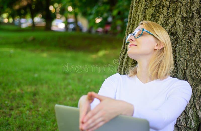 Minuto de la toma para encontrar la inspiración El estudiante prepara proyecto Internet que practica surf del estudiante en parqu foto de archivo libre de regalías