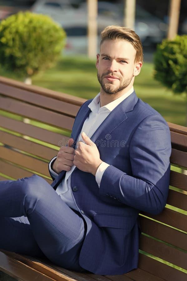 Minuto della presa per rinfrescare i pensieri L'uomo in vestito si rilassa si siede il banco in parco Capo convenzionale dell'abb fotografia stock