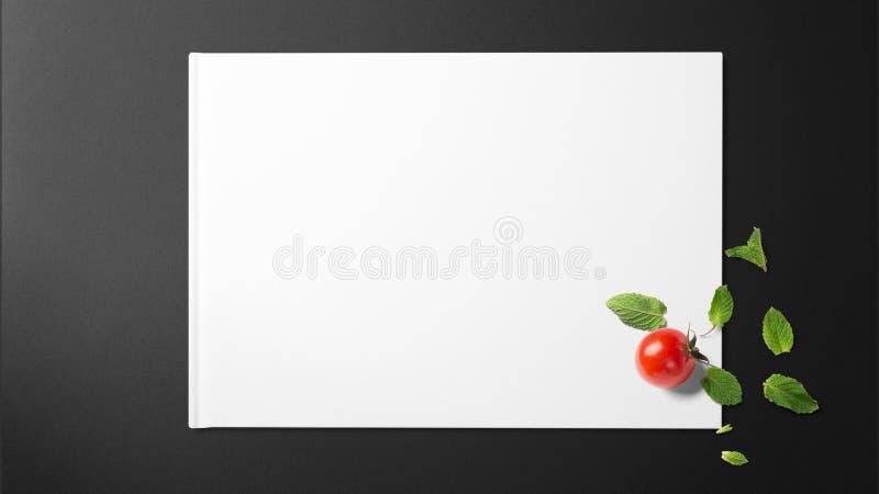 Minze mit Tomate auf Weißbuch auf schwarzem Hintergrund lizenzfreies stockfoto