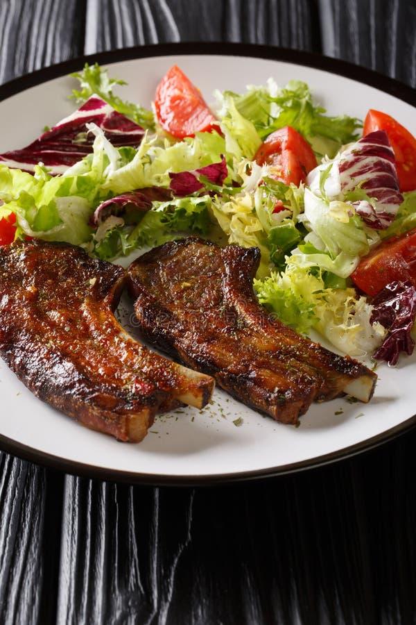Miodowi jagnięcy kotleciki słuzyć z świeżego warzywa sałatką w górę talerza dalej pionowo obraz stock