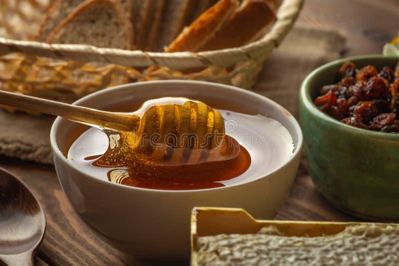 Miodowy garnek i chochla przy wieśniaka stołem z chlebem, rodzynkami i miód gręplą, zdjęcia royalty free
