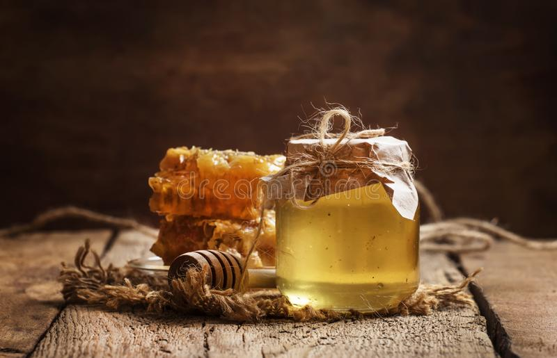 Miodowy słój i honeycomb, rocznika kuchennego stołu drewniany tło, kopii przestrzeń, selekcyjna ostrość fotografia stock