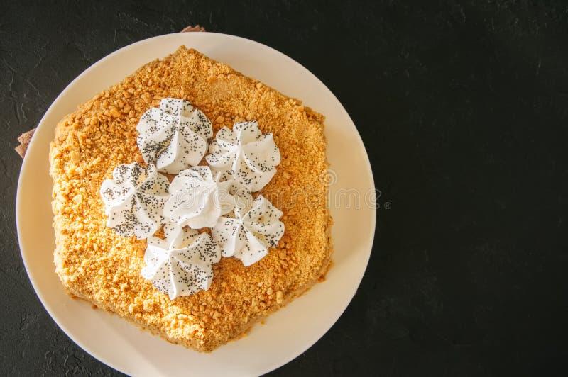 Miodowy tort z bezy dekoracją na wierzchołku słuzyć na białe śliwki fotografia royalty free