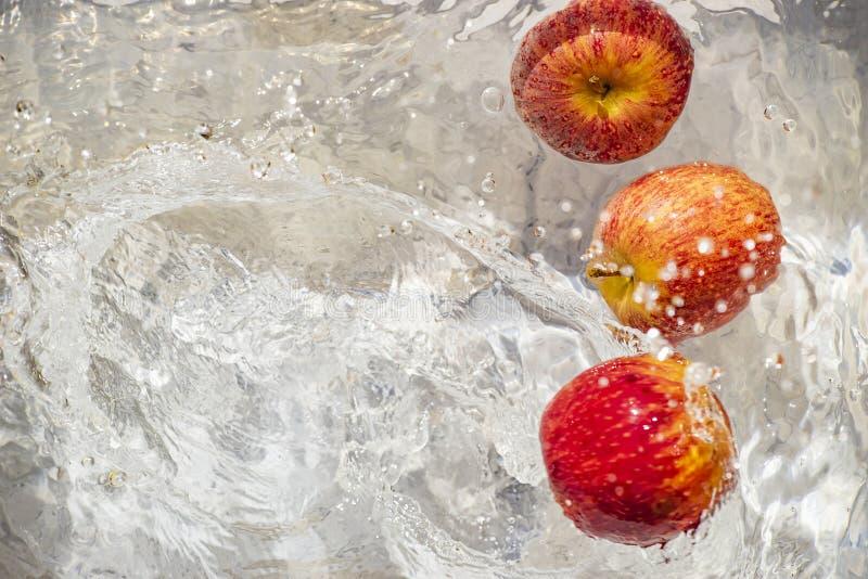 Miotań jabłka czerwoni w wodę zdjęcia stock