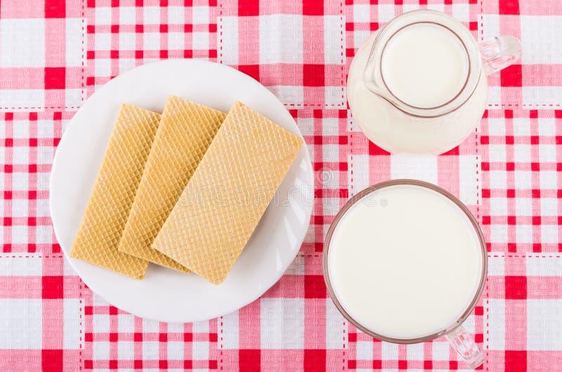 Miotacz i filiżanka z mlekiem, opłatki w talerzu na pielusze zdjęcia stock