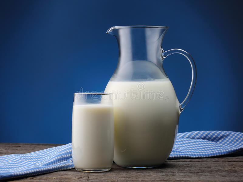 Miotacz i szkło z niektóre mlekiem na błękicie zdjęcie royalty free
