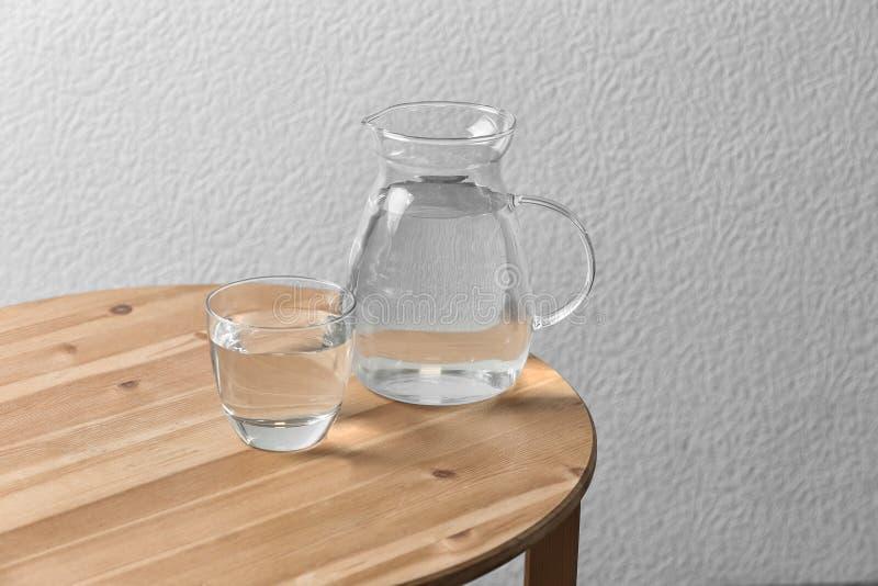 Miotacz i szkło z wodą na stołowej pobliskiej biel ścianie zdjęcia stock