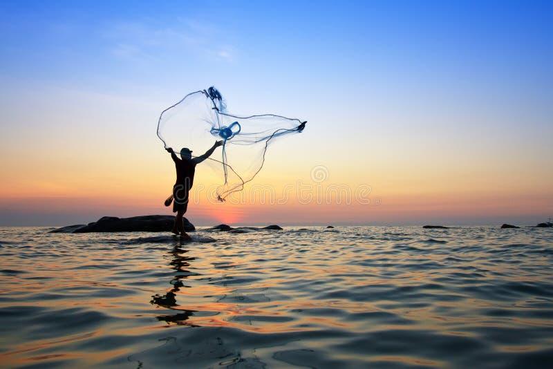 Miotanie sieć rybacka podczas wschodu słońca fotografia stock