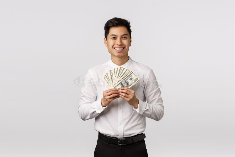 Mira ese dinero Simpático y feliz joven asiático listo para gastar dinero en comprar, sostener dinero y sonreír imagenes de archivo