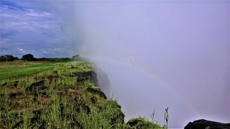 Miracle over Victoria Falls. A rainbow appeared in a thick mist. Of water spray. On the steep slopes of the gorge, bright green grass. There are clouds in the royalty free stock photography