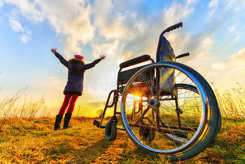 Miracle recovery: young girl gets up from wheelchair and raises hands up. Overjoyed young girl standing up from a wheelchair outdoors. Shot in meadow. Recovery stock photography