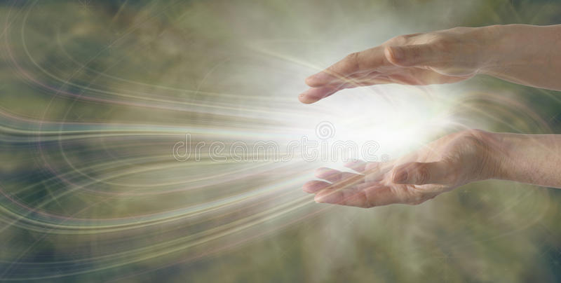 Miracles Happen. Pair of parallel female healer's hands with an intricate white light energy formation between on a wide muted gold background with plenty of royalty free stock photo