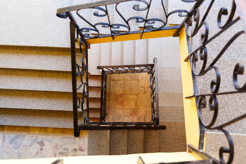 Mirada abajo de una escalera de tres historias foto de archivo