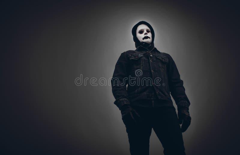 Mirada asustadiza, hombre malvado en capilla negra imagenes de archivo