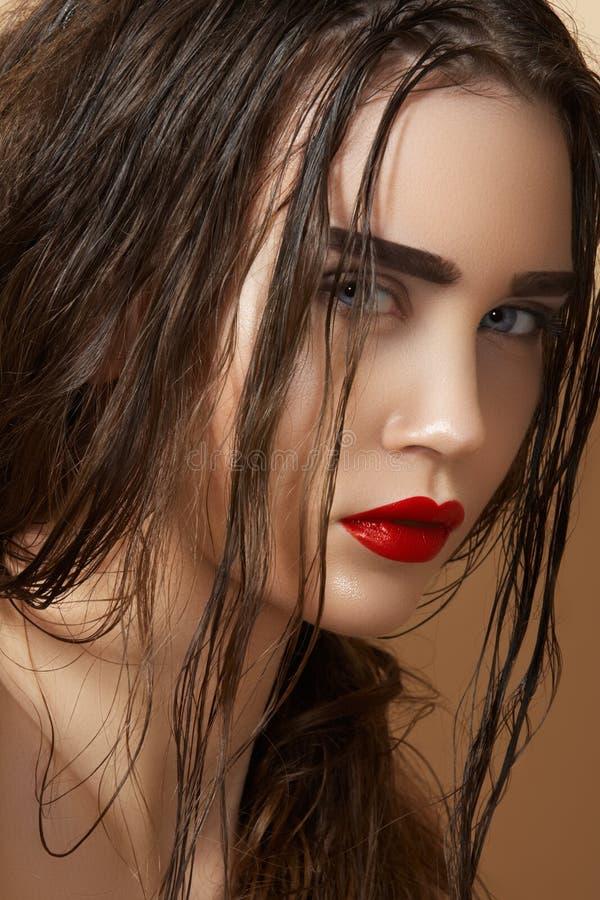 Mirada bochornosa del modelo con el pelo mojado húmedo y el maquillaje fotografía de archivo libre de regalías