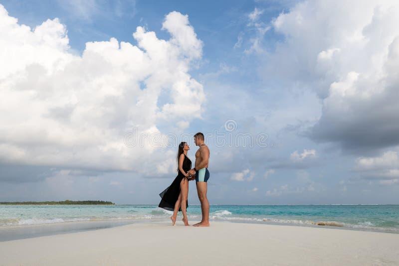 Mirada cariñosa joven de los pares en uno a En el fondo son las nubes y el agua enormes de la turquesa fotos de archivo libres de regalías