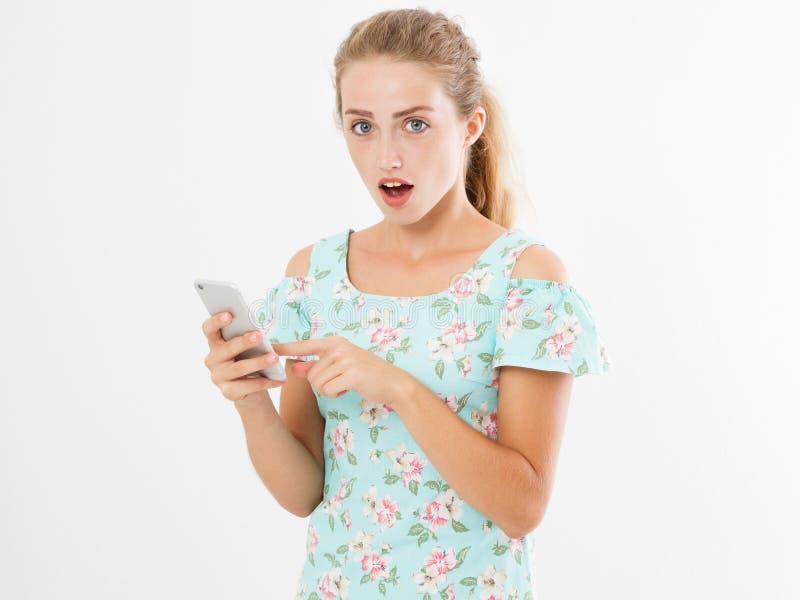 Mirada chocada en el teléfono, la chica joven sorprendida retrato, mujer que mira smartphone viendo malas noticias o las fotos co fotos de archivo libres de regalías