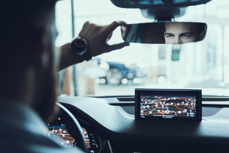 Mirada confiada del hombre de negocios en el coche trasero Mirrow imagenes de archivo