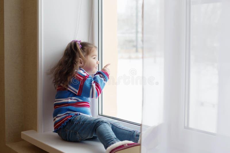 Mirada de la muchacha de la belleza fuera de la ventana imagen de archivo libre de regalías