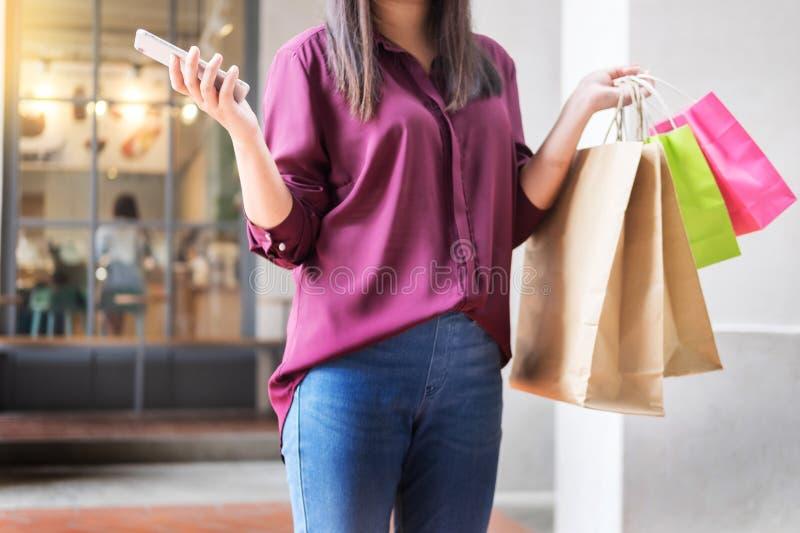 Mirada de la mujer en el teléfono móvil con las bolsas de papel en la alameda mientras que disfruta de compras del día imagenes de archivo