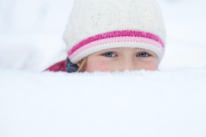 Mirada de la niña fuera de la nieve acumulada por la ventisca con los ojos sonrientes fotografía de archivo